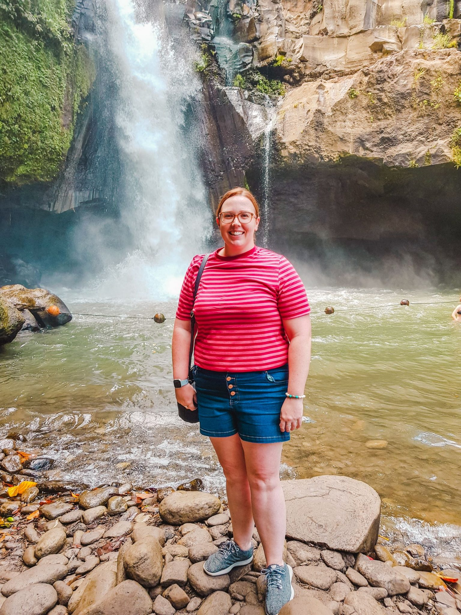 Standing in front of Tegenungan Waterfall in Bali, Indonesia (featuring what to take to Bali)