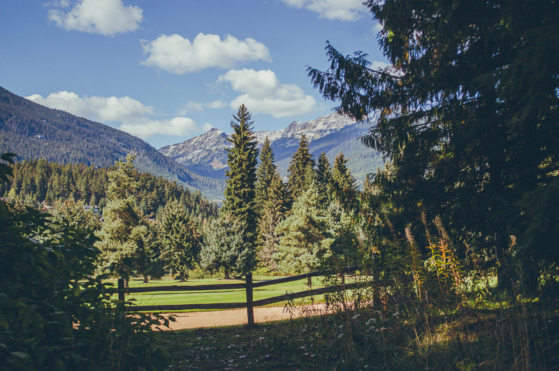 Whistler golf course surrounded by pine trees and rocky mountains (check it out on your Whistler day trip).