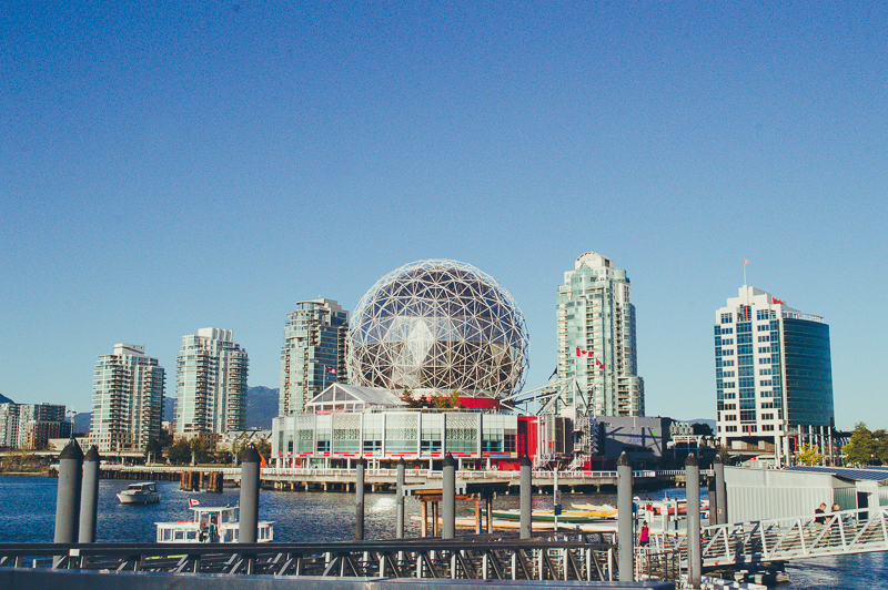 Things to do in Vancouver: visit Science World. Here's a view of the unusual building from Olympic Village; backdropped by apartment buildings and blue sky.