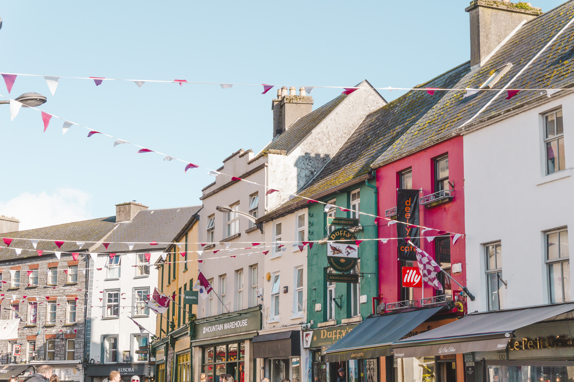 Colourful buildings and flags in Galway, Ireland. Add Galway to your Ireland itinerary and Europe itinerary.
