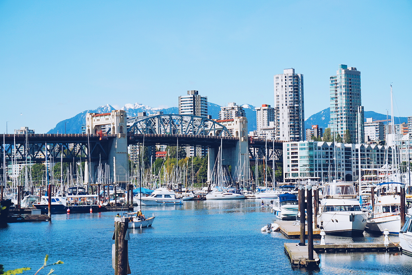 Picture-perfect Vancouver, BC, with boats in a marina, skyscrapers and snowy mountains as a backdrop.
