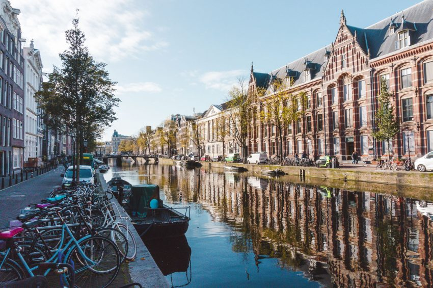 Buildings reflected in an Amsterdam Canal - one of the best solo travel destinations in Europe.