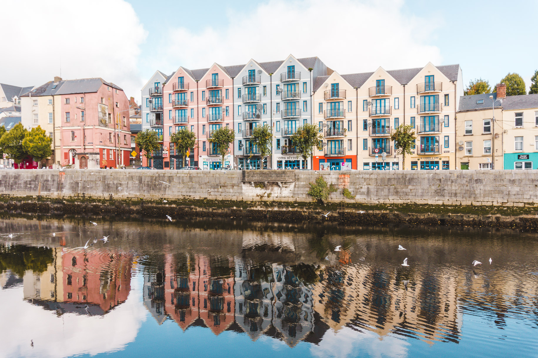 Pastel-coloured buildings reflected in Cork's River Lee. Cork Ireland, day trip from Dublin and a must-visit addition to any Europe itinerary.