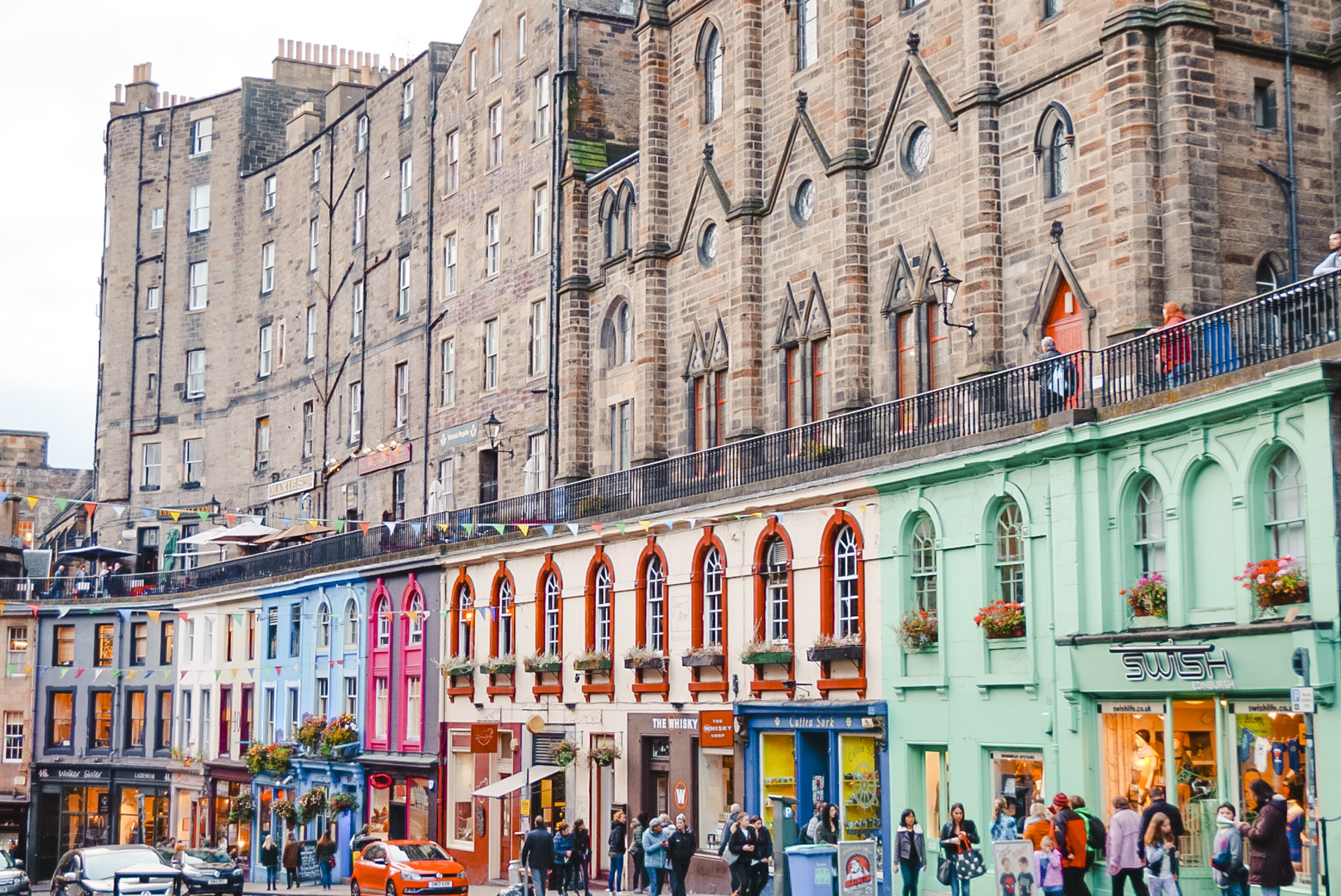 Victoria Street in Edinburgh, which features brick buildings overshadowing colourful Victorian shopfronts. Edinburgh is one of my favourite solo travel destinations.