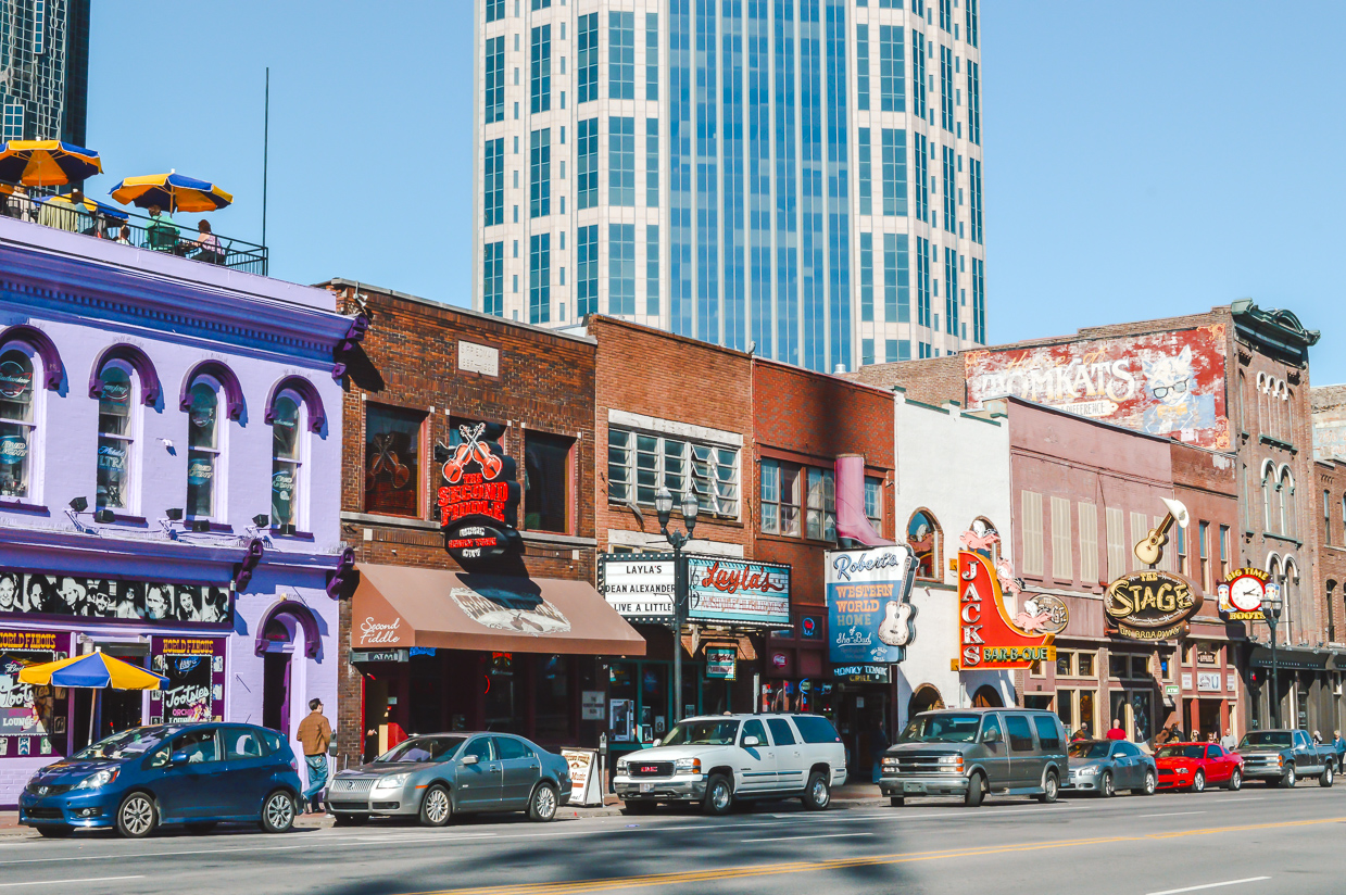 Colourful buildings with large neon signs along Honky Tonk Row in Nashville, one of the best places to travel alone in the US.