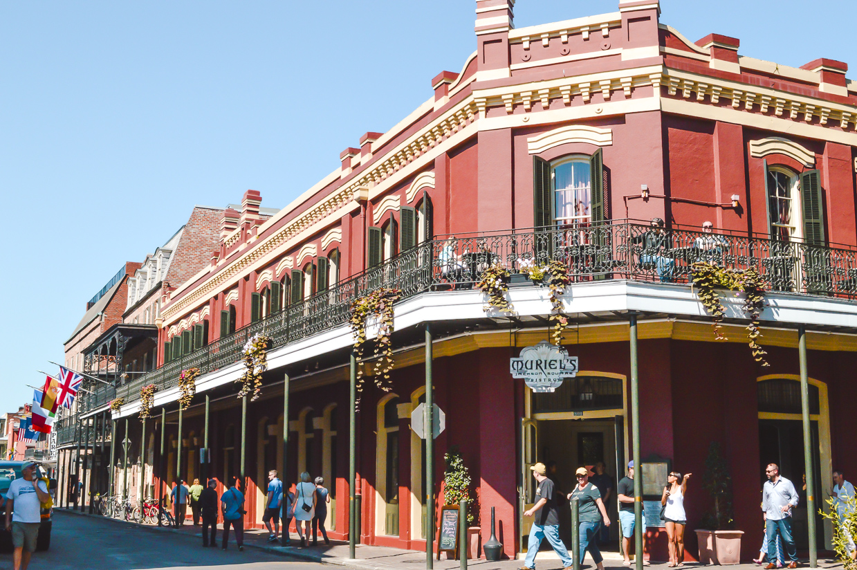 Red two-storey building with full wrought iron balcony in New Orleans, which is one of the best places to travel alone in the US.