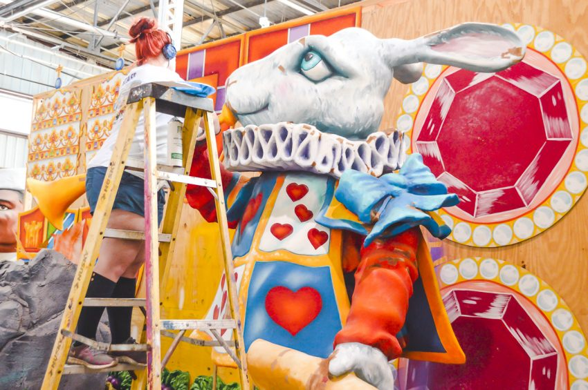 A women painting an Alice in Wonderland-inspired float creation at Mardi Gras World in New Orleans, Louisiana (a great place to vacation alone in the US).