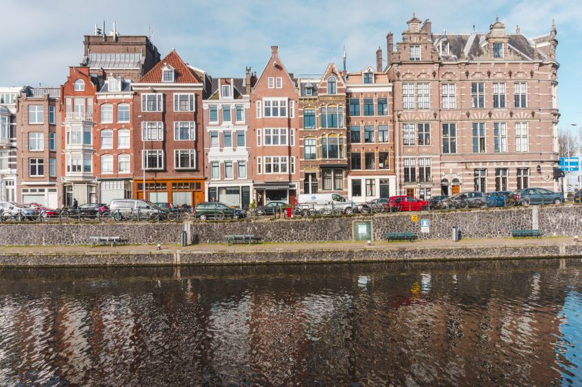 Buildings reflected in a canal in Amsterdam, Netherlands. Amsterdam is a must for any 10-week Europe itinerary.