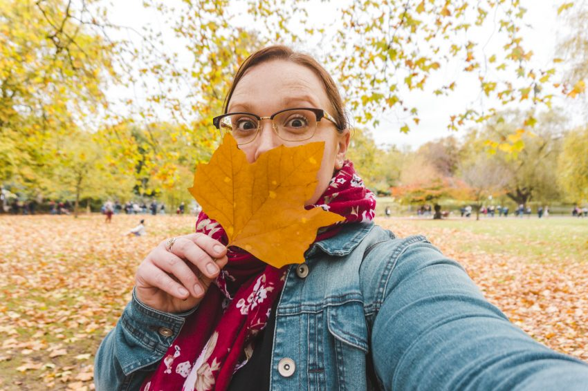 Standing in London's St James Park with a large orange leaf in front of my face. Add London to your UK solo travel itinerary.