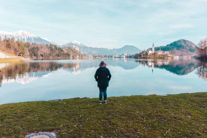 Standing at the edge of Lake Bled with my back to the camera, with snow-capped mountains surrounding me.