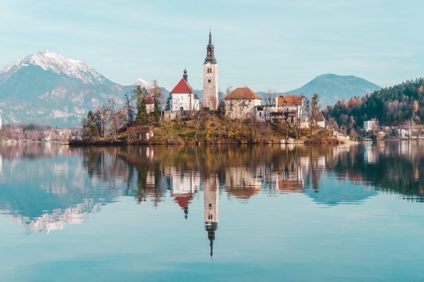 Church on an island in the middle of Lake Bled, with snow-capped mountains in the background.