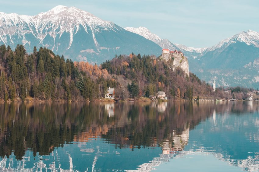 Bled Castle on a rocky cliff top, with the lake in front and snow-capped mountains behind.