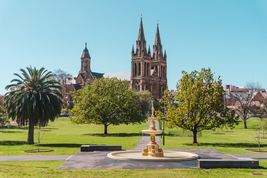 A fountain in front of an old church, surrounded by green grass in Adelaide.