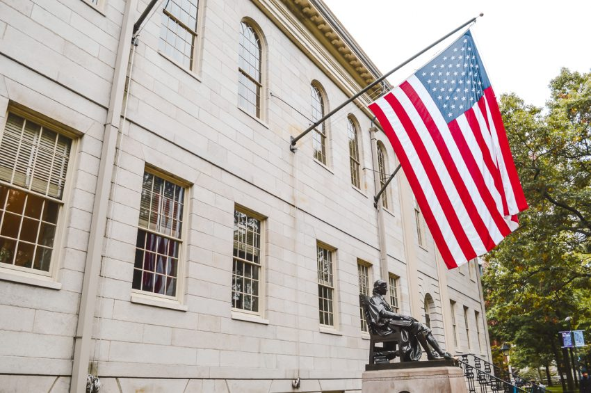 A large American flag hanging from a Harvard University building in Boston. Add Boston to your North America itinerary.