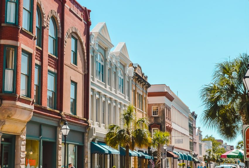 Pretty Victorian buildings and palm trees down the main street in Charleston, South Carolina.
