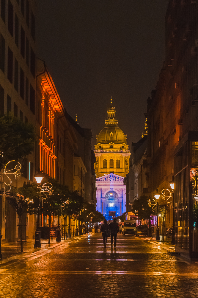 Nighttime view looking down the street towards the glowing St Stephen's Basilica in Budapest.