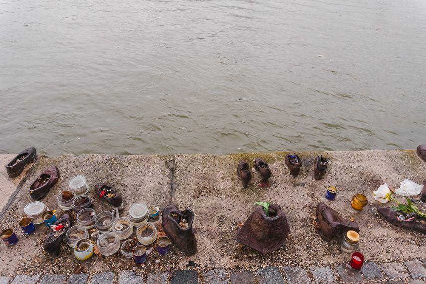 The Shoes on the Danube memorial in Budapest - different bronze shoe statues beside the river.