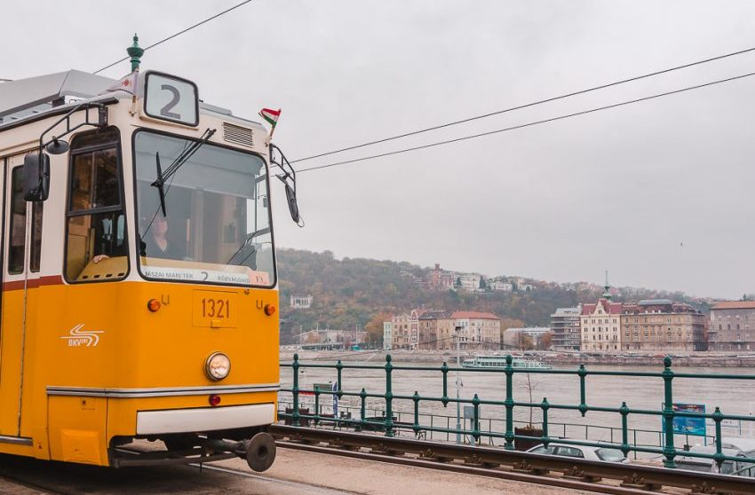 Yellow tram passing by the water in Budapest, Hungary.