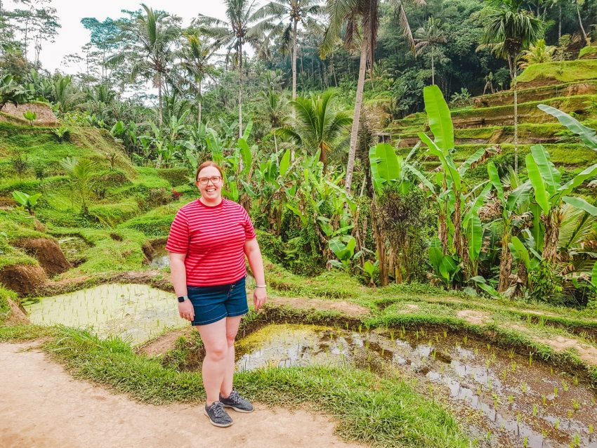 Standing in front of the lush Tegallalang Rice Terraces near Ubud in Bali, Indonesia (solo female traveller in Bali).