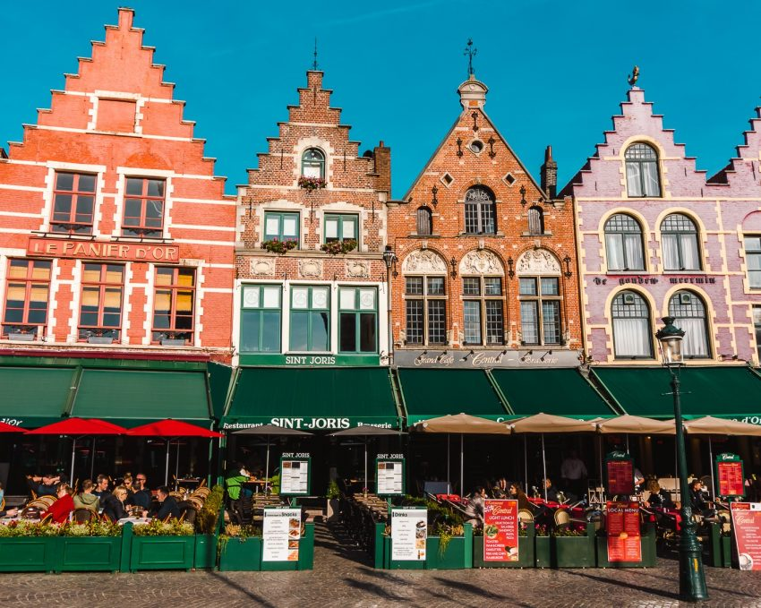 Four colourful Dutch houses with green awnings, backdropped by a bright blue sky in Bruges, Belgium