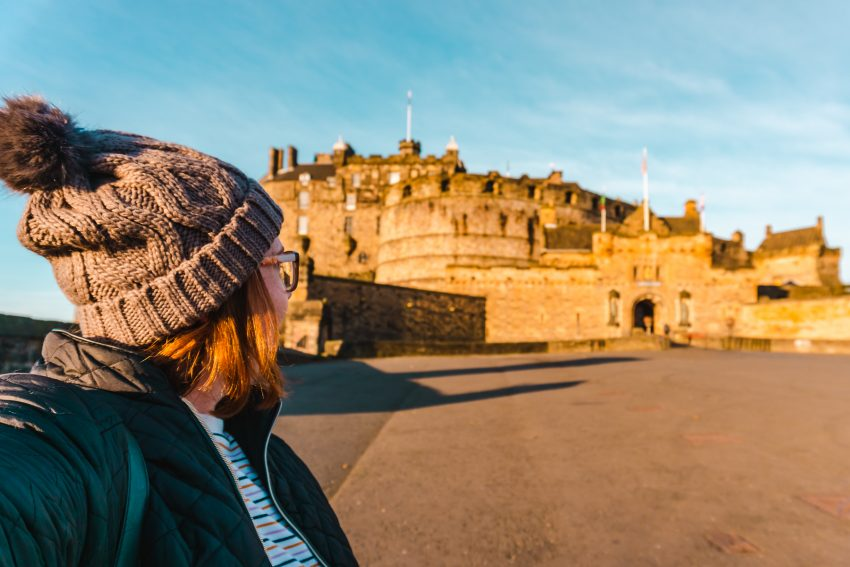 Side profile photo of myself looking towards Edinburgh Castle, glowing in the sunrise light. Welcome to the About page for Australian solo travel blogger and travel content writer, Hayley Simpson.