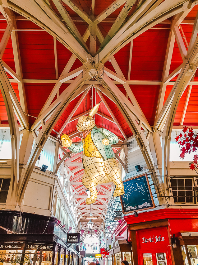 Looking up to a lit Peter Rabbit hanging from the ceiling at Oxford Covered Market in Oxford, England