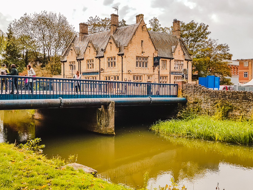 Thatched roof building and blue bridge over Castle Mill Stream in Oxford, England