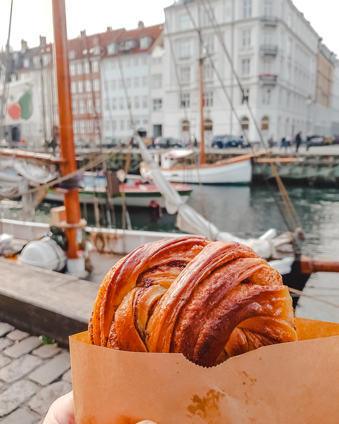 Enjoying a cinnamon bun from Meyers Bageri at Nyhavn in Copenhagen, Denmark.