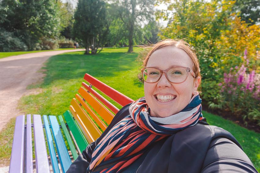 Sitting on a rainbow bench in Gothenburg, Sweden