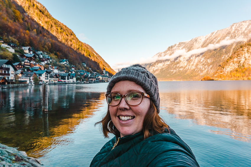 Me standing in front of a lakeside view in Hallstatt, Austria - one of the best day trips from Salzburg.