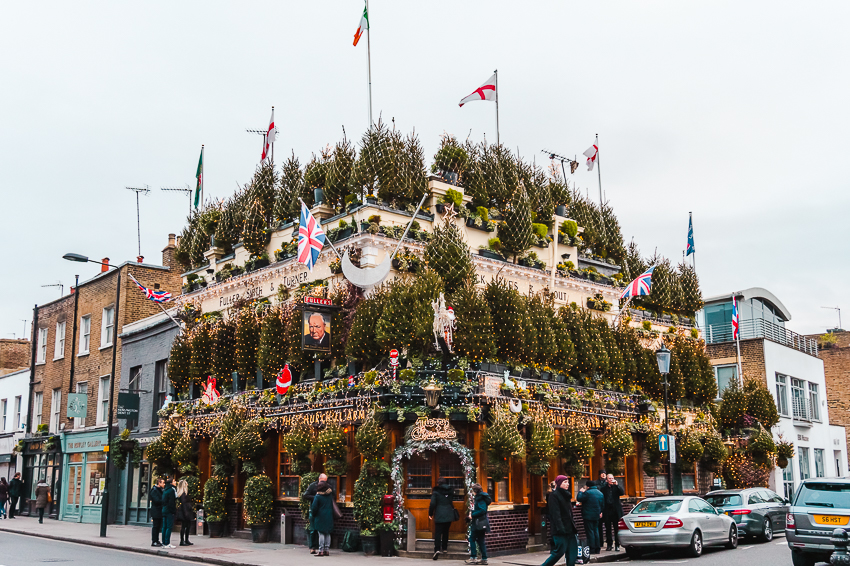 The Churchill Arms pub decorated with Christmas trees in London, England