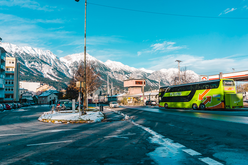 FlixBus parked in front of snowy mountains in Innsbruck, Austria (Europe budget travel tips)