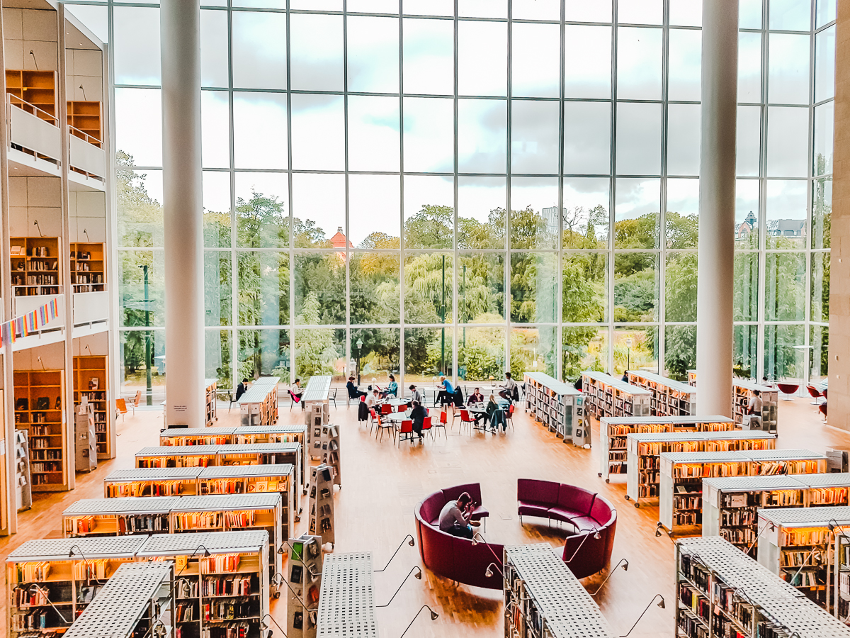 Things to do in Malmo, Sweden - visit the City Library, with a multi-story glass window looking out to a park.
