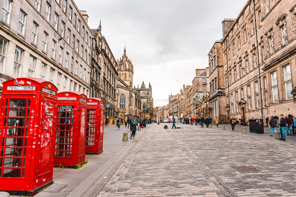 Red phone boxes and quiet cobblestone street in Edinburgh's Old Town
