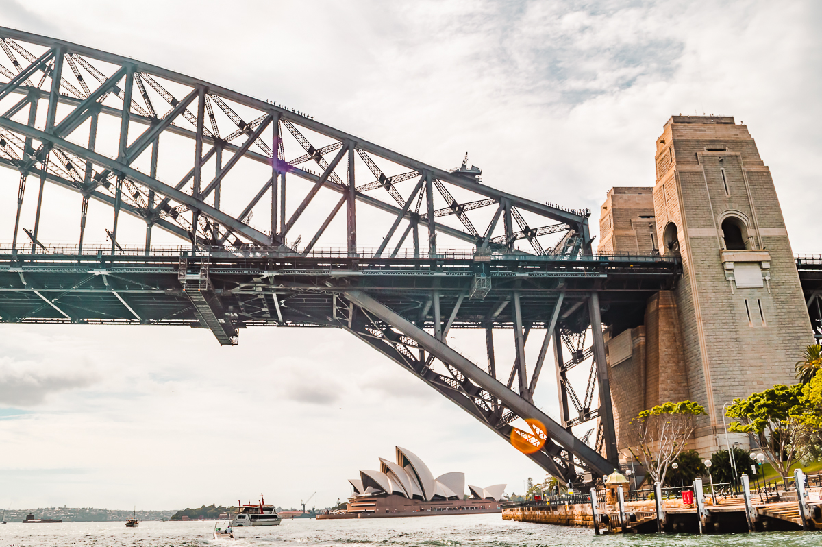 The Sydney Opera House peeking out underneath the Sydney Harbour Bridge.