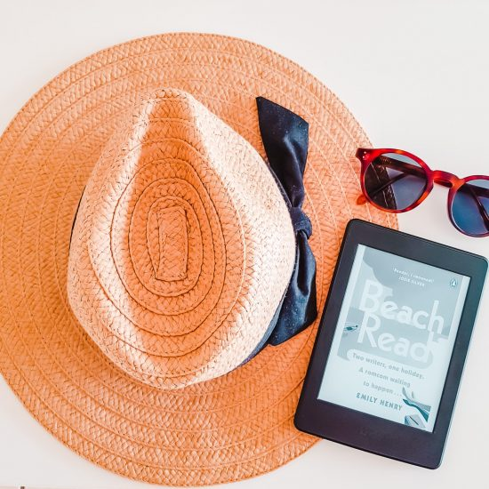 Straw hat, glasses and a Kindle displaying Beach Read, one of the best new release books in 2020.