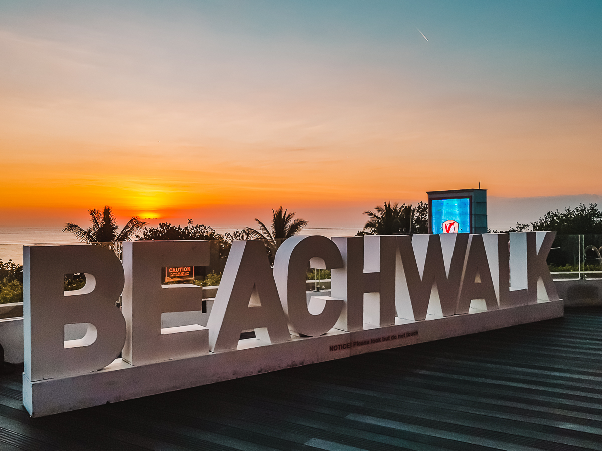 Beachwalk sign in front of orange sunset over Kuta Beach in Bali (solo travel in Bali).