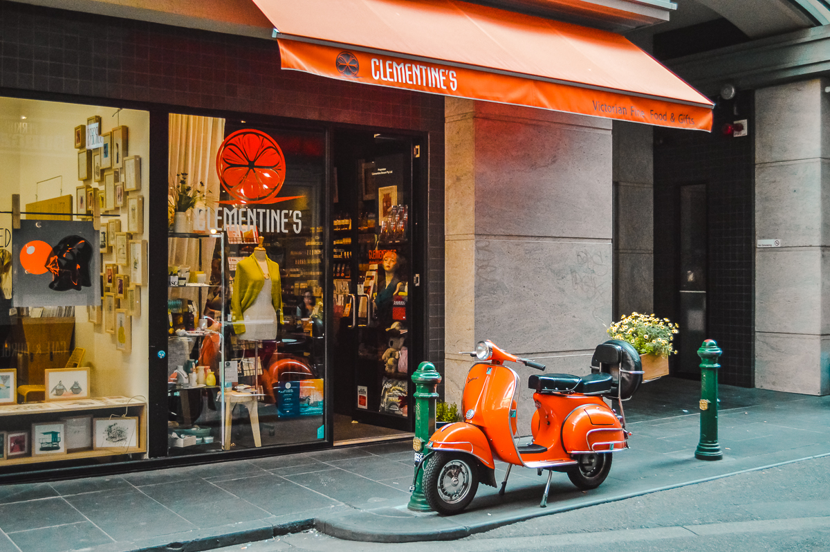 Melbourne's European vibes are evident along Degraves Street, where an orange scooter is parked outside a shop front with an orange awning.
