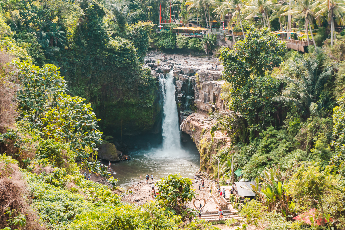 Looking across to Tegenungan Waterfall in Bali, which is surrounded by lush greenery.