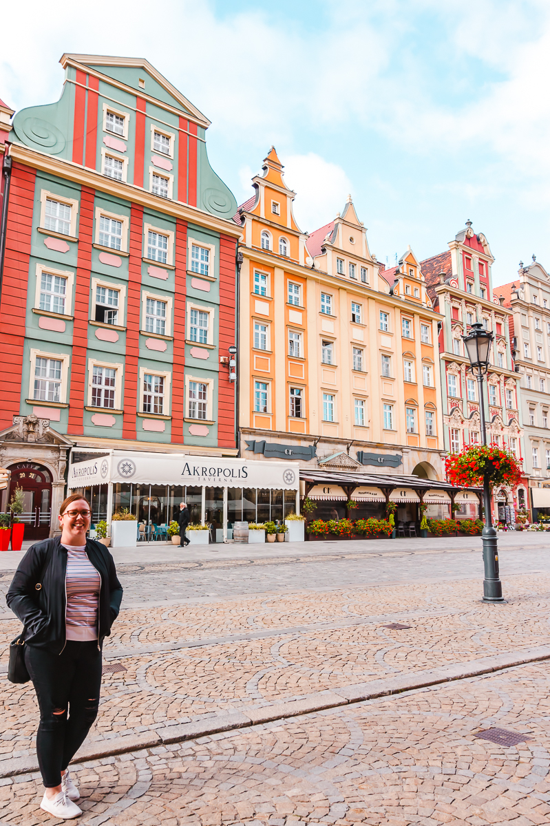 Standing in front of colourful buildings in the Market Square in Wroclaw's Old Town.