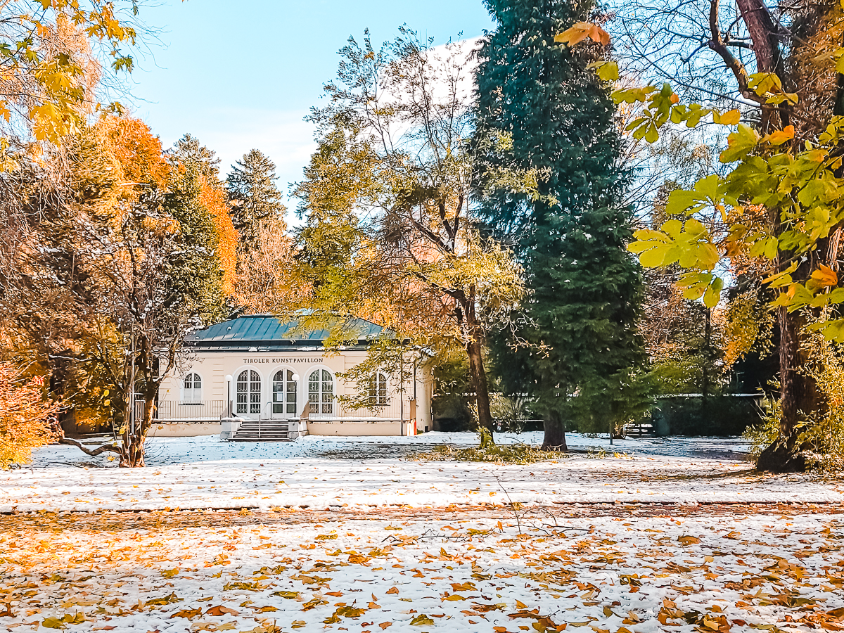 Fall leaves and snow on the ground in Innsbruck Hofgarten. Check it out on an Innsbruck day trip from Munich.