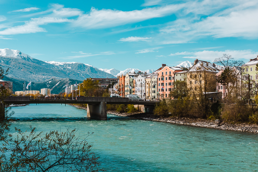 Aquar river and colourful buildings and snowy mountains in the distance in Innsbruck, Austria.