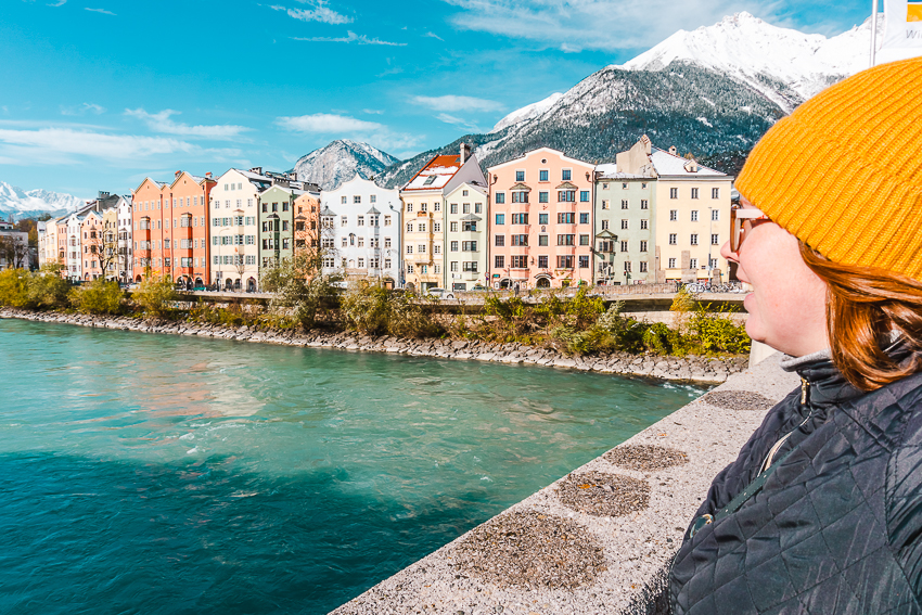 Side profile, looking over aqua river to colourful buildings in Innsbruck, Austria.