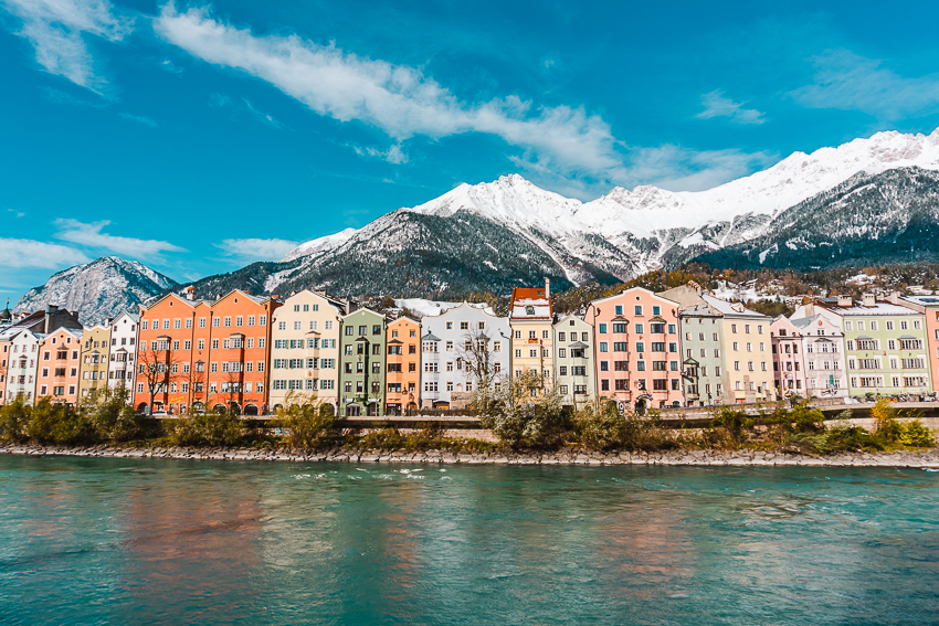 Colourful buildings and snow-capped mountains in Innsbruck, Austria. I definitely recommend doing an Innsbruck day trip from Munich.