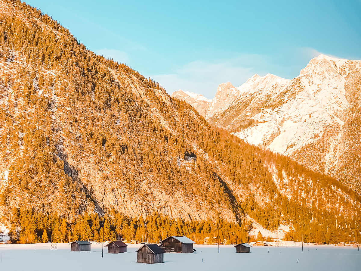 On the bus from Munich to Innsbruck, with a golden glow on a passing hill and small buildings in the snow.