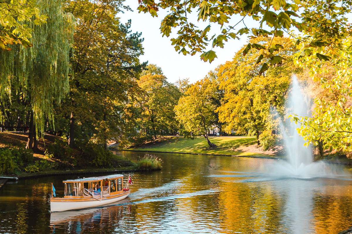 Boat and fountain on river flowing through Bastejkalns Park in Riga, Latvia.